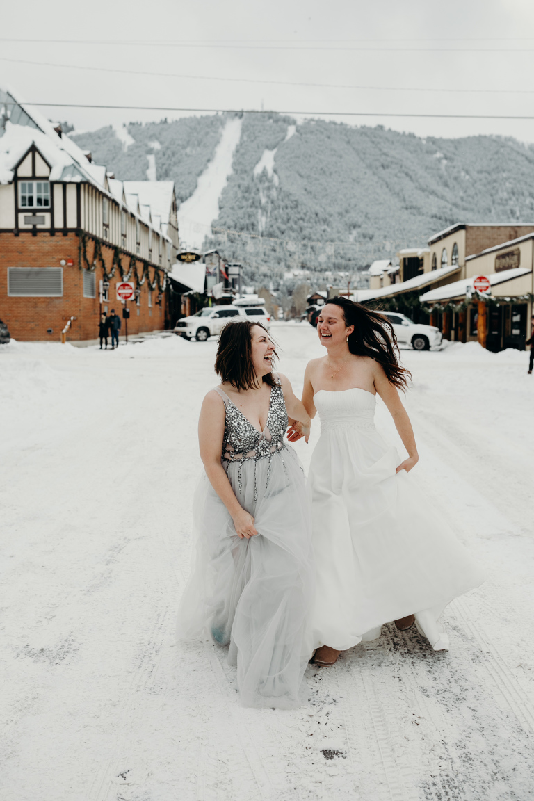 two brides run down the snowy streets of Jackson Hole, Wyoming