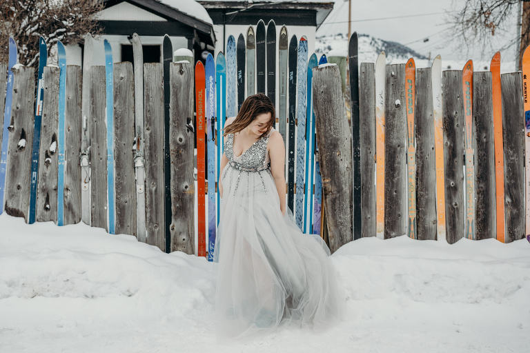 a bride swooshes her winter wedding gown in front of a ski fence in Jackson Hole